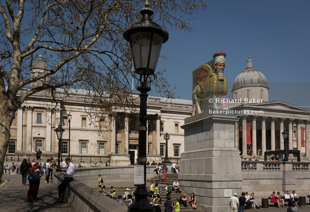 The 12th Fourth Plinth commission by the Mayor of London  artwork entitled 'The Invisible Enemy Should Not Exist' by the artist Michael Rakowitz, in Trafalgar Square, on 19th April 2018, in London, England. Started in 2006, the sculpture recreates over 7,000 archaeological artefacts looted from the Iraq Museum during the war there or destroyed elsewhere. Oneof these was Lamassu, a winged deity which guarded Nergal Gate at the entrance to the ancient city Assyrian city of Nineveh (modern-day Mosul, Iraq) which was destroyed by ISIS in 2015. The Lamassu, which had the same footprint as the Fourth Plinth is made of empty Iraqi date syrup cans, representative of a once-renowned industry.