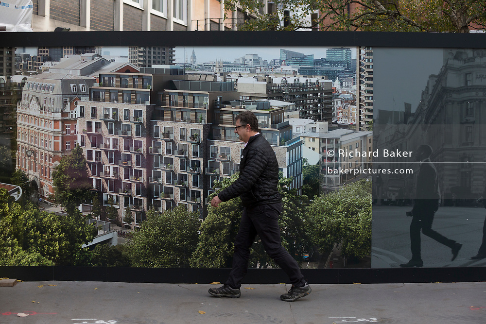 """A pedestrian walks past a construction hoarding for the new luxury apartment development called The Denizen, a controversial 10-storey building by Taylor Wimpey that locals say will dominate their view and block their daylight, on 30th October 2017, in London, England. Residents from Bowater House on the Golden Lane Estate have erected banners by artists Jeremy Deller and Elizabeth Price to picket the developers. Despite this, Wimpey say, """"We are one of the UK's largest residential developers. As a responsible developer we are committed to working with local people and communities."""""""