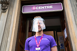 Edinburgh, Scotland, UK. 28 July, 2020. Business and tourism slowly returning to the shops and streets of Edinburgh city centre. Employee at VisitScotland tourist information office on the Royal Mile in the Old Town , in PPE wearing face screen. Tourists numbers are increasing tin the Old Town.  Iain Masterton/Alamy Live News