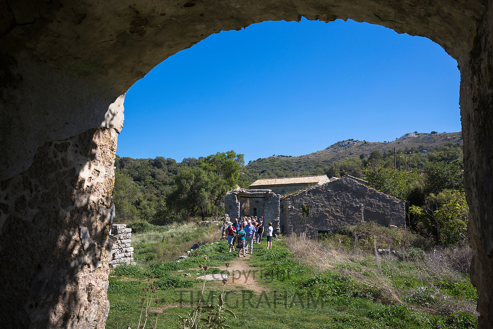 Tourists visiting house ruin in oldest village of Corfu - ancient Old Perithia - Palea Perithea, Greece