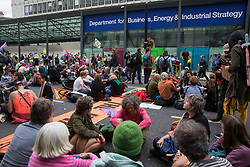 Environmental activists from Extinction Rebellion, Stop HS2, XR Roads Rebellion and Paid to Pollute hold crisis talks outside the Department for Business, Energy and Industrial Strategy (BEIS) following the Stop The Harm march on the fourth day of Impossible Rebellion protests on 26th August 2021 in London, United Kingdom. Extinction Rebellion are calling on the UK government to cease all new fossil fuel investment with immediate effect.