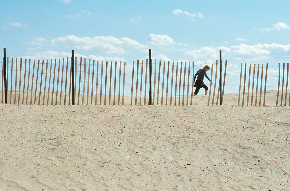 A person walking on the beach behind a broken fence