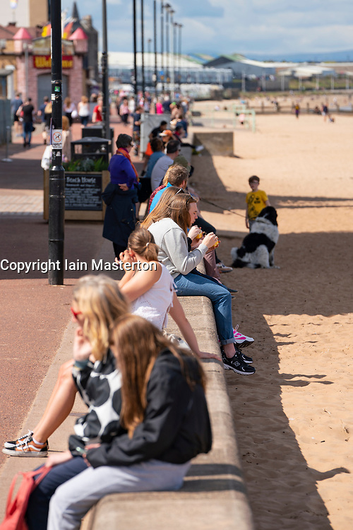 Portobello, Scotland, UK. 8 May 2020. Images from Friday afternoon during Covid-19 lockdown on promenade at Portobello. Promenade and beach were busier than in recent weeks due to warm sunny weather and the fact that several cafes and takeaway food shops are now open. Police patrols were low key. Pictured; people sitting on promenade with takeaway food and ice cream. Iain Masterton/Alamy Live News