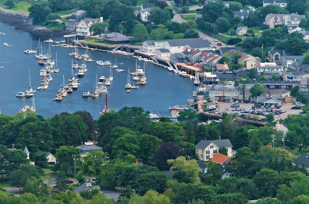 This is a view of Camden Harbor in the summertime. The saliboats fill the harbor, the tree are in full leaf, people and cars are everywhere.