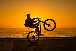 ©Licensed to London News Pictures.28/03/2019. Aberystwyth, UK. A beautiful sunset , at the end of another day of warm spring sunshine, silhouettes a young man doing wheelies on his bike,  enjoying  the warm evening on the promenade in Aberystwyth, on the Cardigan Bay coast of west Wales. High pressure continues to dominate the weather for much England and Wales, with settled conditions forecast to last at least another day , before more cooler conditions return. Photo:Keith Morris/LNP