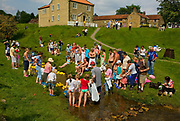 Hutton Le Hole, picturesque village on the Yorkshire moor, England, UK.<br /> Summer visitors by the stream. Plastic duck race.