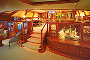 The main salon of Hyperion, widely considered one of the world's finest sailing yachts, built by the Royal Huisman Shipyard in Vollenhove, Holland.  An electric organ folds out beneath the model ship and the dining table is motorized to accommodate guests against sliding into the couch seating.  Over 7000 different fucntions on the boat are controlled by computers.  And although the yacht is one of the most elegant interior and exterior designs in the world she is also one of the fastest, winning the Millinium Cup, a race of super-yachts during the last America's Cup.