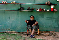 Enrique Cordova, of Hidalgo, Mexico sits outside of the community house that he shares with over thirty men. Cordova has worked at the farm for ten years.