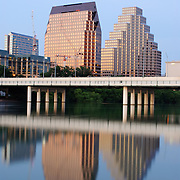 Austin skyline in the twilight with two tall modern buildings, including the Radisson Hotel, in downtown Austin reflected on Town Lake. In the middle of the frame is the Congress Avenue Bridge. Vertical/portrait orientation.