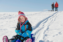 Portrait of girl sledging down hill while her parents watching, Bavaria, Germany