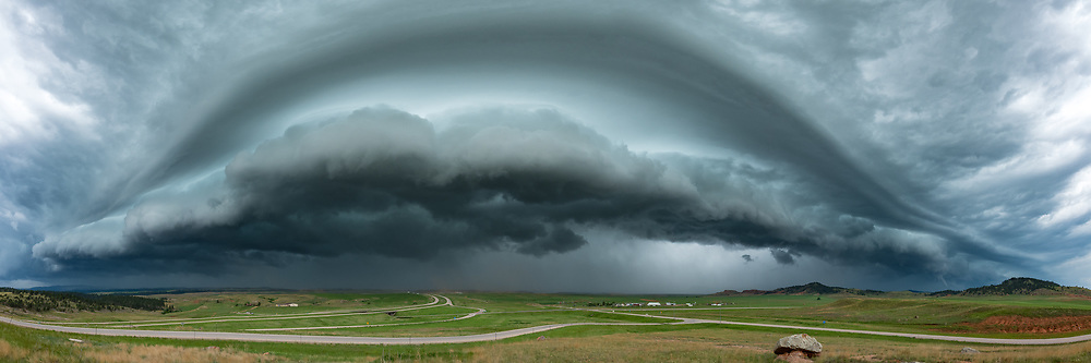 Pictured is a highly unusual weather event called a derecho. Derechos are a long-lived wind storm that may travel across multiple states and cause widespread damage. They occur a few times a year in the Midwest or Eastern US. What was unusual about this derecho is that it began in Utah at 9AM. Normally the Rockies disrupt organized storm systems, but this one had no problem plowing 750 miles all the way to North Dakota. Hundreds of wind reports ranged from 60 to 110 mph. I intercepted the squall line near the Wyoming/South Dakota border. The severe thunderstorm warning mentioned a storm motion of 100 mph which was a bit difficult to comprehend. I tried to make it to a mountaintop, but then had to go with plan B, which turned into plan C which was pretty much the side of a road off of I-90. The shelf cloud was very ominous. The air was notably calm and quiet just before it struck. One mountain after another vanished into the rain and dust. Then seconds later the wind was roaring and I couldn't even stand up straight.