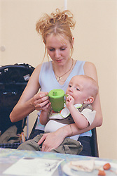 Mother holding and feeding baby at Surviving Homelessness Project,