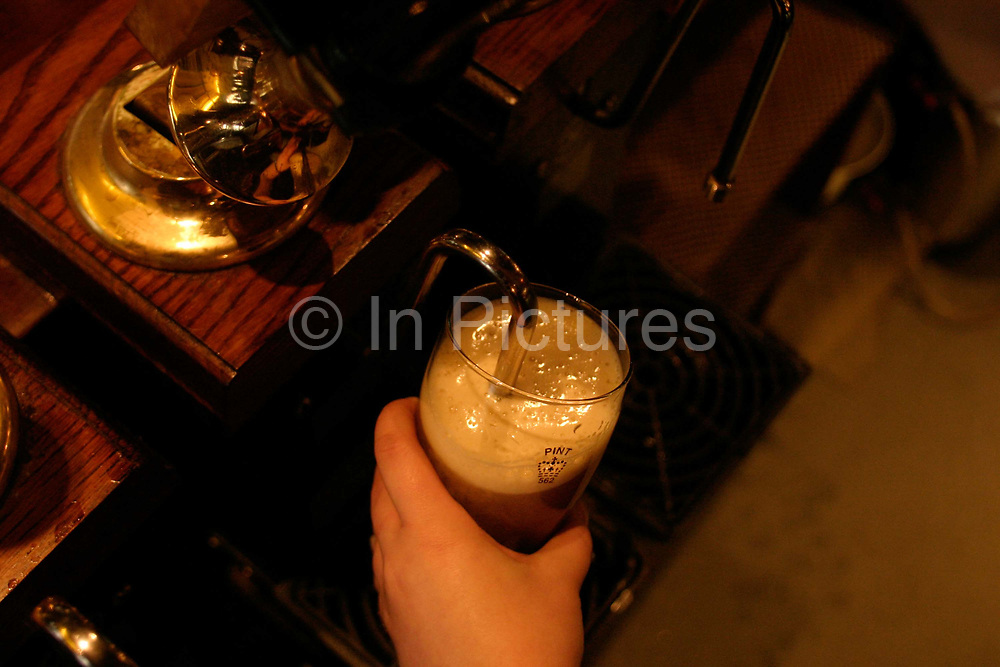 A barmaid pulls a pint of beer in the Jamaica Inn Public House, London, UK