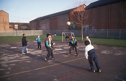 Group of boys playing game of football in school playground,