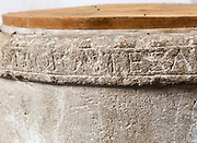 """Circa 10th century Anglo-Saxon baptismal font, around its rim is a Latin inscription  from Psalm 42: """"Sicut cervus desiderat ad fontes aquarum ita desiderat anima mea ad te deus amen"""": """"As a deer longs for the running brooks, so longs my soul for you, O God"""" inside the church at Potterne, Wiltshire, England, UK"""