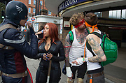 Friends dressed up as superheroes meet up in West London. They are on their way to a comic convention where fans of amination gather, dressing up as their favourite characters. UK. Teenage Mutant Ninja Turtles, Captain America and Black Widow, Natasha Romanov