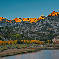 The sun rises over the Eastern Sierra Nevada above North Lake and fall-colored aspens in Bishop Creek Canyon near Bishop, California.