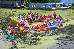 © Licensed to London News Pictures. 30/07/2019. London, UK. People canoeing in Regents Canal covered in Algae during rainfall in north London. Photo credit: Dinendra Haria/LNP