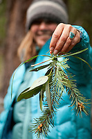 Young woman holding handmade bunch of forest gatherings.