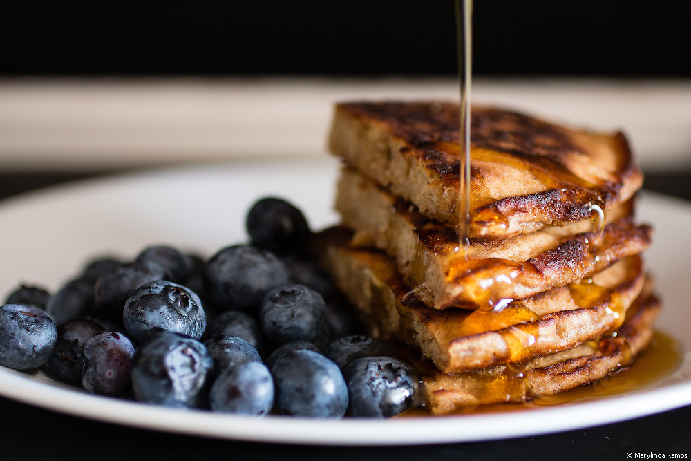 A thin drizzle of syrup runs down this quarter-stack of pancakes with a side of fresh blueberries.