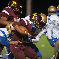 Tohatchi's Mario Perez carries the ball as he is tackled by Zuni's defense Friday night at Tohatchi High School.
