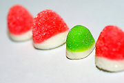 A line of red colourful sugared jelly sweets with one green one in the centre