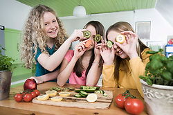 Girls in kitchen making faces with fruit