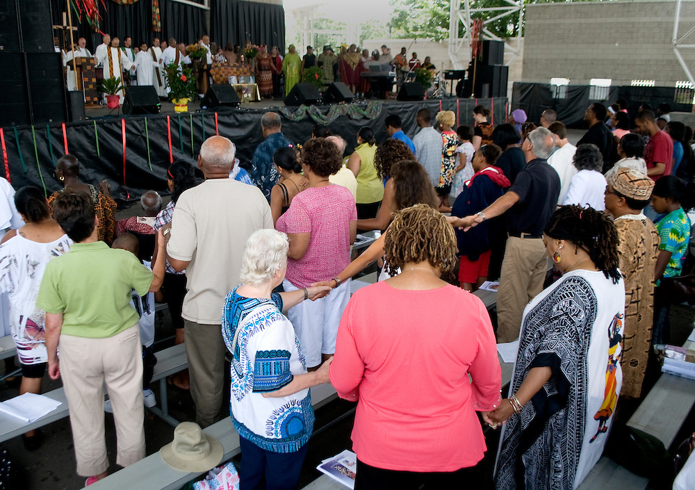 Attendees hold hands during the mass, Sunday, Aug. 1.