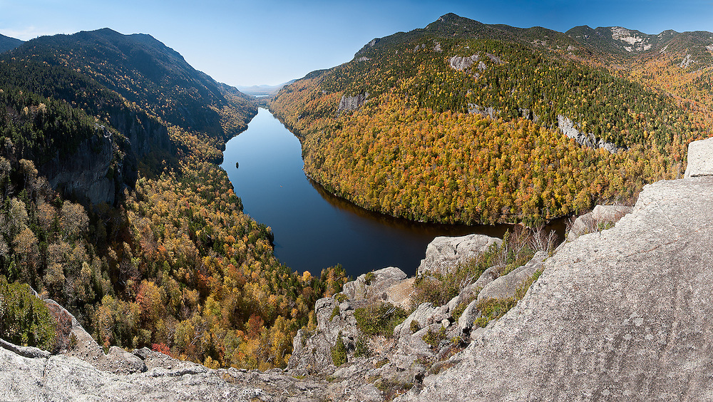 Lower Ausable Lake, Adirondacks, NY.<br /> <br /> At the far end of the Adirondack Mountain Reserve, I clambered around the cliffs of Indian Head.  The peaks of Colvin and Blake continued the ridge to my left, and the mountains of the Great Range-Sawteeth, Gothics, and Armstrong--faced me to the west.  Below, a couple of red pixels against the blue is a canoe, barely leaving a wake on the surface of Lower Ausable Lake.  The lake pierces the two ranges like a giant exclamation, with the Upper namesake as the point.  This is a stitch of 5 vertical images.