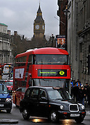 © Licensed to London News Pictures. 16/12/2011, London, UK.  The bus, behind a famous black taxi cab, drives up Whitehall. The first bus designed specifically for London arrived in the capital today, carrying the Mayor of London BORIS JOHNSON. The bus design is based on the famous red route master buses with a rear platform for access. Photo credit : Stephen Simpson/LNP
