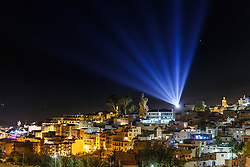 View of Chefchaouen against Rif Mountains at night, lit by spotlight in sky, Morocco