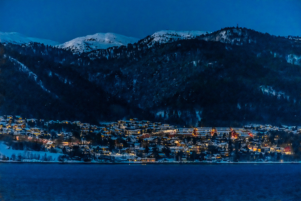 The city of Molde at twilight, in winter, Norway. A lighted ski slope can be seem above the city.