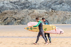 Two surfers walking to the sea at Fistral in Newquay, Cornwall.