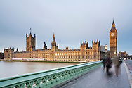 Early morning commuters crossing Westminster Bridge on a winter's dawn looking towards the Houses of Parliament, London, Uk