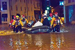 © Licensed to London News Pictures. 24/02/2020. Shrewsbury, Shropshire, UK. A man and a woman are rescued. The Shropshire Fire and Rescue Service carry out an evacuation operation in the Coleham area of Shrewsbury in Shropshire as the River Severn levels continue to rise UK causing severe flood disaster situations. The Environment Agency forecast levels to peak tomorrow evening at around 5.56 metres. Photo credit: Graham M. Lawrence/LNP