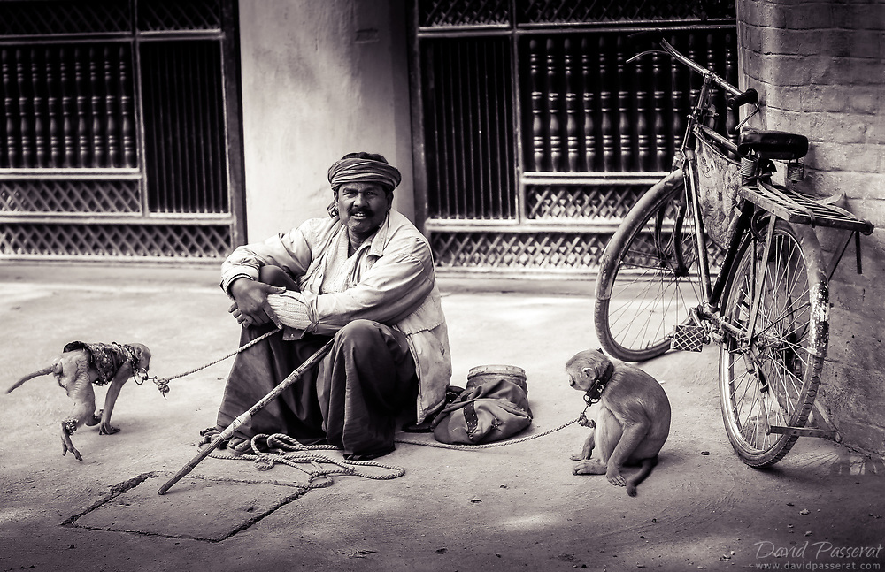 Monkey trainer in the street with his two monkeys.