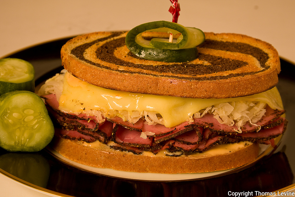 Full size reuben sandwich on a black plate with melted swiss cheese, thousand Island, all on marbled rye. Raw to JPEG