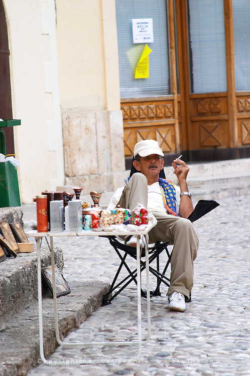 The busy old market bazaar street Kujundziluk with lots of tourist craft and art shops and street merchants. Street merchant in lazy laid-back pose on a lounge chair selling cigarettes, perfume, dolls and other souvenirs. Historic town of Mostar. Federation Bosne i Hercegovine. Bosnia Herzegovina, Europe.