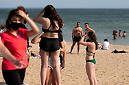 A woman stands in her bikini with friends at St Kilda Beach during COVID-19 in Melbourne, Australia. Premier Daniel Andrews comes down hard on Victorians breaching COVID 19 restrictions, threatening to close beaches if locals continue to flout the rules. This comes as Victoria sees single digit new cases. (Photo by Dave Hewison/Speed Media)