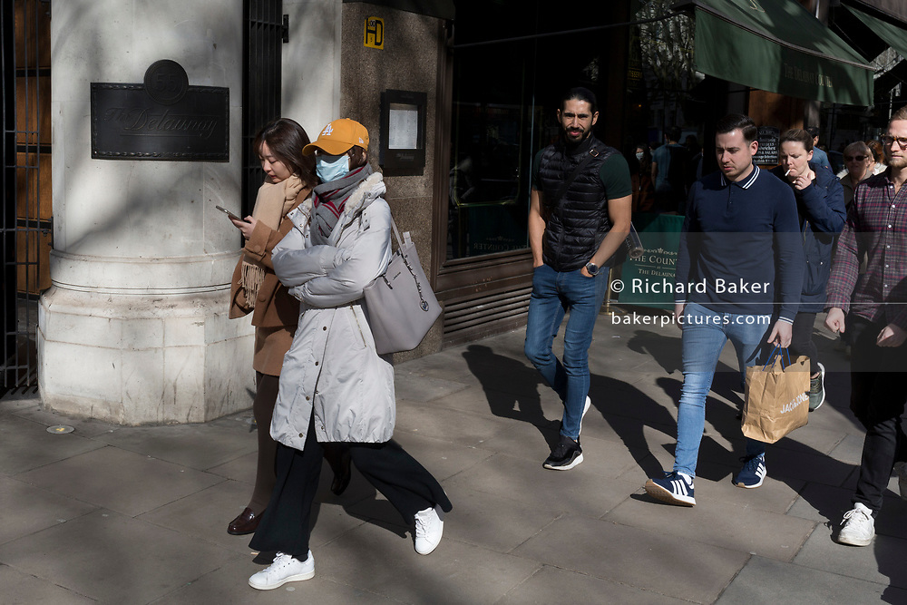 On the day that the UK Government's Chief Scientific Advisor, Sir Patrick Vallance said that the Coronavirus Covid-19 outbreak was now spreading person to person in the UK, foreign students wearing surgical masks walk along Aldwych during their lunch-hours, from nearby London School of Economics (LSE), on 6th March 2020, in London, England.