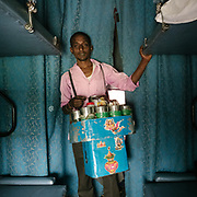 Peddler selling Pan, chewing tabacco. Throughout the journey, peddlers pop into the train compartments with all sorts of offerings,  to be bargained for a few rupees.<br /> Inside the Dibrugarh-Kanyakumari Vivek Express, the longest train route in the Indian Subcontinent. It joins Kanyakumari, Tamil Nadu, which is the southernmost tip of mainland India to Dibrugarh in Assam province, near the border with Burma.