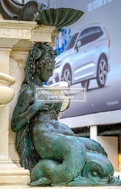 Close up detail from the Fontana del Nettuno, with a modern car advertisement on the poster in the background.<br /> <br /> (c) Andrew Wilson | Edinburgh Elite media