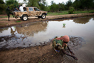 Soldiers smear mud on pick up trucks before driving through areas recently bombed by the SAF airforce in order to make the cars less visable from the air.