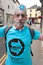 © Licensed to London News Pictures. 27/07/2019. Brecon, Powys, Wales, UK.A Brexit supporter wears a mock Jeremy corbyn mask as Des Parkinson, retired former Welsh police chief superintendent and Brexit Party candidate for the Brecon & Radnorshire constituency, continues his campaign in Mid Wales to win the seat in the forthcoming by-election on 1st August 2019.<br /> The by-election has been recalled because the incumbent Tory MP Chris Davies has been booted from the seat after a recall petition was passed when more than 10,000 voters backed the move. <br /> The Brexit Party was founded by former UKIP economics spokeswoman, Catherine Blaiklock in January 2019, and is led by Nigel Farage. The Brexit party has 29 Members of the European Parliament (MEPs) and four Welsh Assembly Members. The party's first major electoral success was winning the 2019 European Parliament election in the United Kingdom after four months in existence. Photo credit: Graham M. Lawrence/LNP