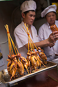 A vendor sells bird on a stick in Yu Gardens bazaar Shanghai, China