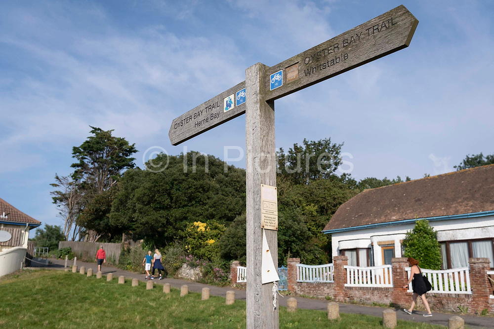 A signpost for the Oyster Bay Trail points to the east-west route between along the north Kent coast, a theme for the local historically-farmed shellfish, on 25th July 2021, in Whitstable, Kent, England. The Oyster Bay Trail is a 6.7 mile, 10.7km walking and cycling route, an extension to the renowned Viking Coastal Trail which links Reculver Country Park to Bishopstone, Herne Bay and Swalecliffe.