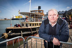 """© Licensed to London News Pictures. 04/05/2016. Birkenhead UK. Picture shows Dan Cross who bought the Daniel Adamson in 2004 for £1 from the Manchester Canal Ship Company. The Daniel Adamson steam boat has been bought back to operational service after a £5M restoration. The coal fired steam tug is the last surviving steam powered tug built on the Mersey and is believed to be the oldest operational Mersey built ship in the world. The """"Danny"""" (originally named the Ralph Brocklebank) was built at Camel Laird ship yard in Birkenhead & launched in 1903. She worked the canal's & carried passengers across the Mersey & during WW1 had a stint working for the Royal Navy in Liverpool. The """"Danny"""" was refitted in the 30's in an art deco style. Withdrawn from service in 1984 by 2014 she was due for scrapping until Mersey tug skipper Dan Cross bought her for £1 and the campaign to save her was underway. Photo credit: Andrew McCaren/LNP ** More information available here http://tinyurl.com/jsucxaq **"""