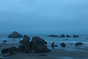 Numerous sea stacks dot the Oregon coastline at Bandon on a foggy morning. The area's most famous sea stack, Face Rock, is visible near the horizon at the left side of the image. According to Indian legend, Face Rock is a tribe member who was turned to stone by an evil spirit who lives in the Pacific Ocean.