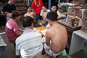Men playing cards at a pet shop market in Shanghai, China.