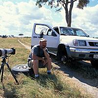 Africa, Botswana, Chobe National Park, (MR) Photographer Paul Souders sits by broken safari truck in Kalahari Desert